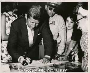 John F. Kennedy signs the guest register at the in the Alamo. To his left is his sister Patricia Lawford and to his right the DRT hostess, Jacqueline Runnels Espy.