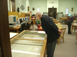 Library visitors look at items on exhibit from the collection.