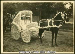 Two women in a decorated carriage, circa 1900-1910.