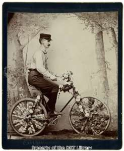 C.M. McAmis, photographed in a studio, riding the bicycle he decorated for the 1893 parade.
