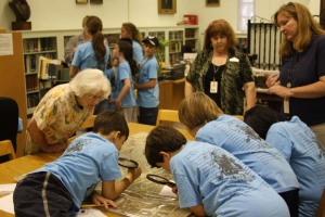 Assistant Director Martha Utterback, bookkeeper Madalene Morgan, and Alamo museum educator Sherri Driscoll assist campers in closely examining an 1873 map of San Antonio.