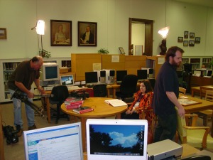 """Crew members from the television show """"Texas Country Reporter"""" adjust lighting and cameras in the reading room while Cecilia Cheever, Alamo Mission Chapter DRT and member of the Library Committee, looks on."""