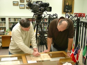 Bob Phillips and a member of the crew examine a letter written by Alamo defender Daniel William Cloud letter.