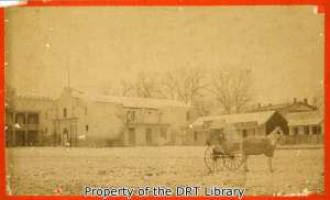 A photograph from the late 1800s showing a saloon operating immediately to the south of the Alamo church. (SC13523)