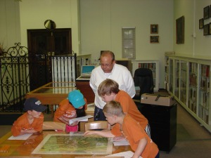 Reference Librarian Chuck Tucker works with campers as they get a closer look at an 1873 map of San Antonio.