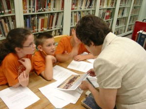 Cataloging Librarian Beverly Ewald shows students a reproduction of a Theodore Gentilz painting.