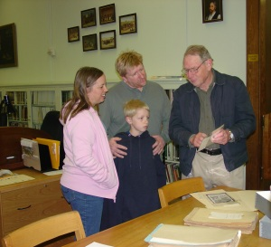 Russell Howard shows Amy Howard Herpeche, her husband, and her husband a picture of A.J. Sowell in the DRT Library's photograph collection.