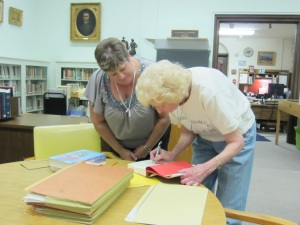 Madge Thornall Roberts, 2011-2013 Library Committee Chairman and a descendant of Sam Houston, signs a copy of her book on the Houston family for Belinda Markovich, a teacher at Luna Middle School in San Antonio and a Houston fan.