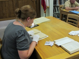 Jennifer Sandoval, a teacher at The Winston School San Antonio, examines Anna Gibbs McKinney's handwritten nineteenth-century book of recipes and home remedies.