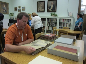 John Smetzer, a teacher at Coke Stevenson Middle School in San Antonio, examines scrapbooks during his visit to the DRT Library.