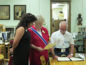 Melinda Navarro and Karen Thompson read a proclamation prepared by representatives of the Alamo Bar as Bill Chadwick presents it aloud.
