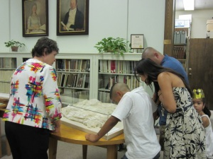 Cataloging Librarian Beverly Ewald (left) talks to a family about a petticoat that belonged to Alamo survivor Angelina Dickinson.