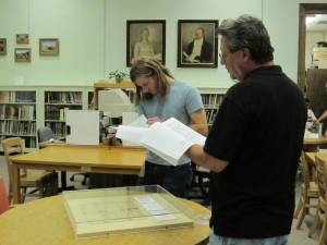 Two visitors compare the original Daniel Cloud letter with a transcription of the document during the Library's Founders Day Open House.