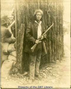An unidentified actor portraying David Crockett in front of the reconstructed Alamo palisade.