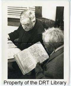 "Photographer Dick McConnaughey writes: ""Father Carmen Tranchese is shown with Don Leandro Granada, grand old man of the Guadalupe Church's Pastores troup. He is shown holding his second copy of the original Pastores. It is from this copy that Father Tranchese made his translation which is being printed in both Mexican and English."" Los Pastores, Col 928, Daughters of the Republic of Texas Library, San Antonio, Texas."
