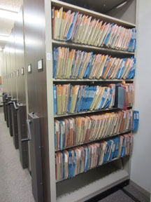 "The Vertical Files are stored on moveable ""compact shelving."" This allows us to maintain our large collection of over 70,000 files in as small a space as possible."